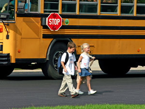 Picture of stopped school bus with kids crossing street